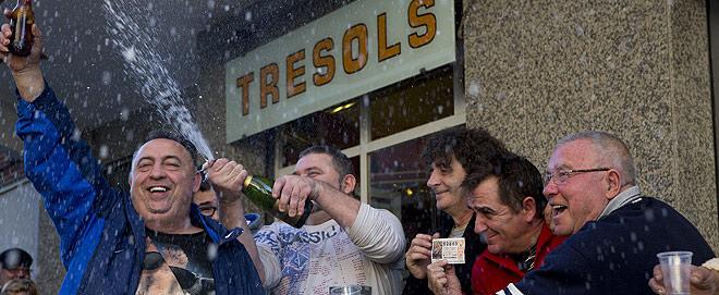 El due�o del Bar Tresols de Gav� descorcha una botella de cava para celebrar el segundo premio con varios clientes.