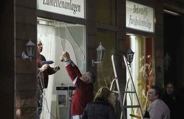 Unos hombres reparan los escaparates de una tienda rotos por los manifestantes ultraderechistas en Leipzig.