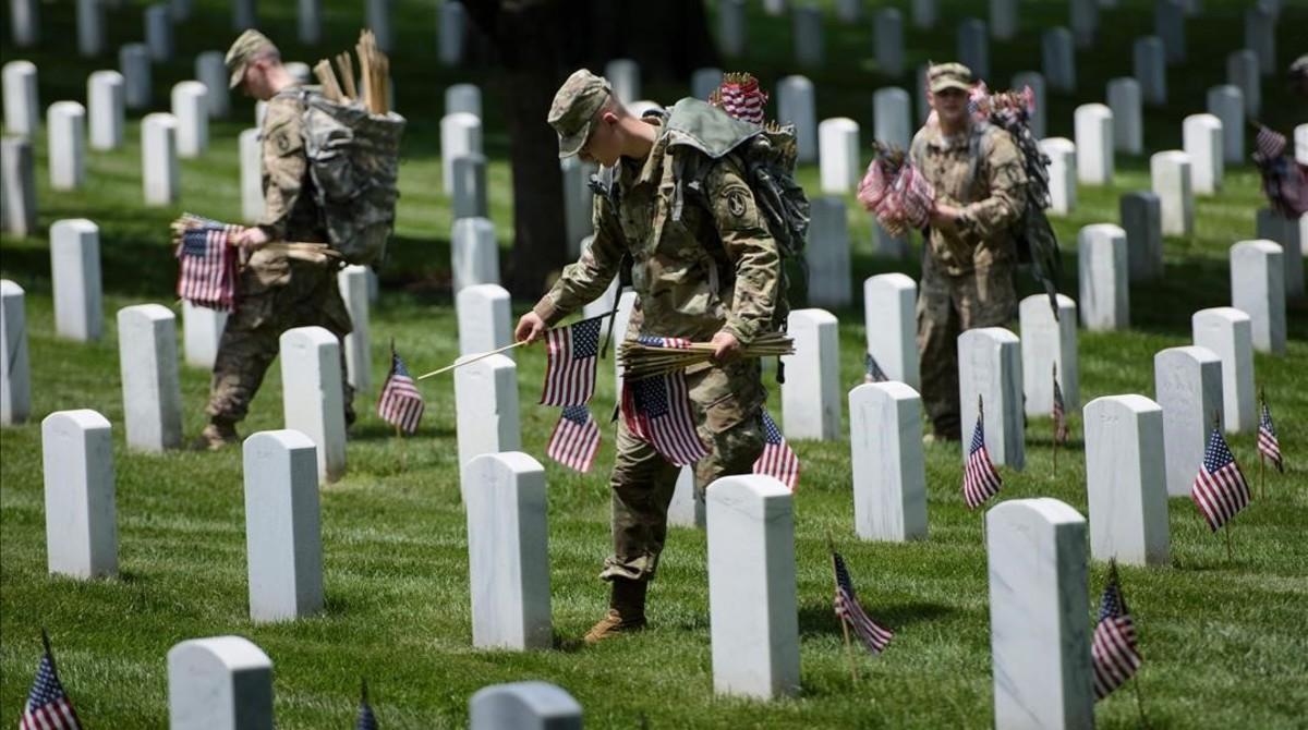 Soldados de EEUU colocan banderas en las tumbas del cementerio de Arlington (Virginia), el 26 de mayo.