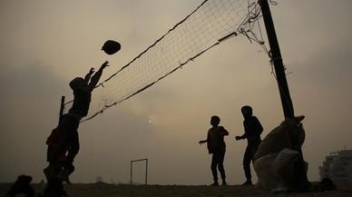 Niños palestinos juegan al voleibol con una pelota de plástico cerca de sus casas en la ciudad de Gaza.