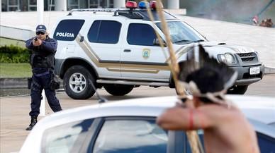 Un policía apunta con su arma a un indígenaarmado con un arco y flechas frente al Congreso de Brasilia.