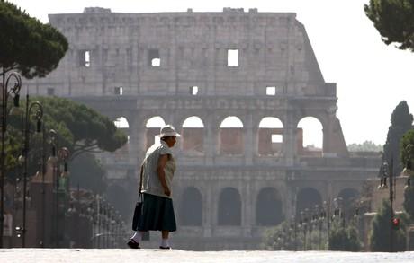 Una mujer pasea por el Foro Imperial ante el Coliseo de Roma.