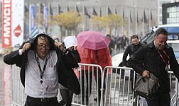 Participantes en el Mobile World Congress tratan de protegerse de la lluvia.