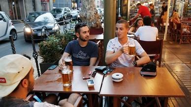 Unos turistas consumiendo jarras de cerveza en el centro de Barcelona.