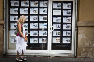 Una señora pasa delante de una oficina de alquileres de pisos.