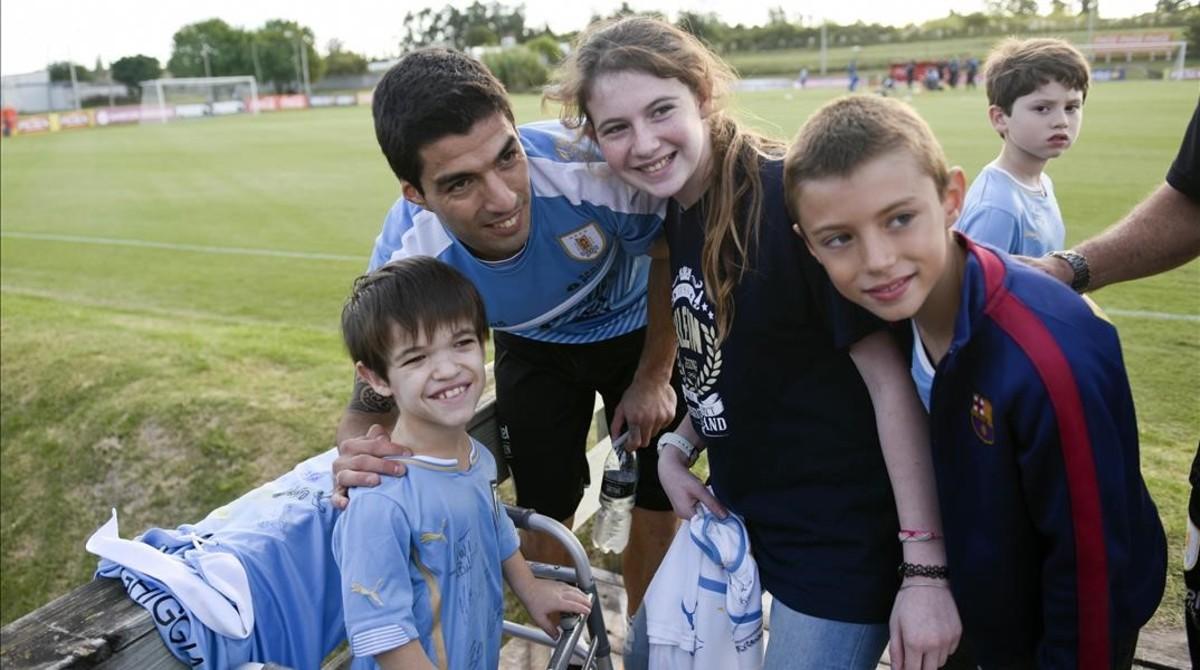 Luis Suárez posa con una jóvenes aficionados tras su primer entrenamiento con la selección uruguaya.
