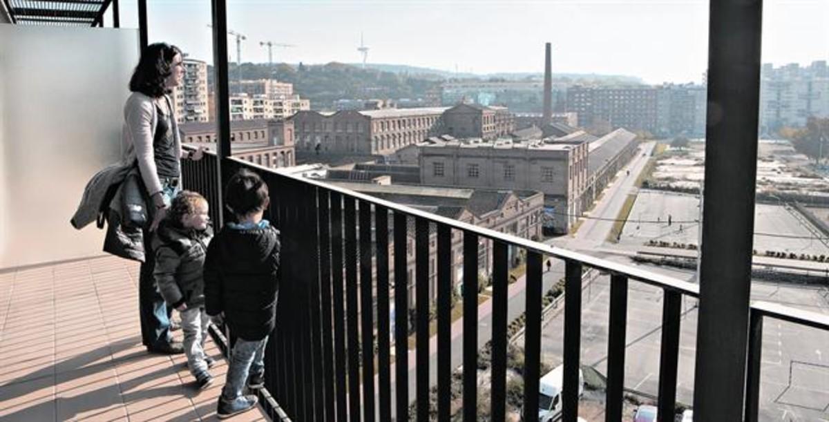 Viviendas en Can Batlló. Una familia admira las vistas desde su futuro piso.