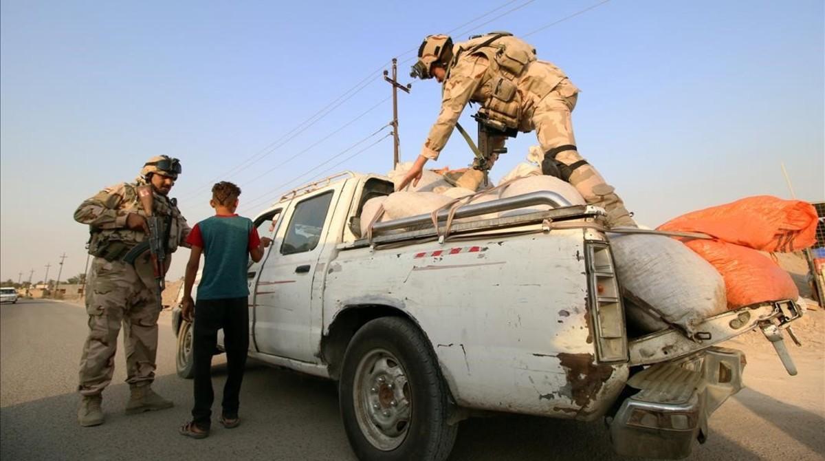 Soldados iraquís inspeccionan vehículos en el norte de Irak.