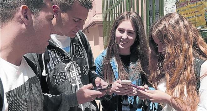 ESPERANÇA.CAT.Jóvenes consultan la 'app' de ayuda a gente de su edad.