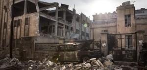 Imagen de un coche incendiado y de edificios destruidos en el barrio de Saif Al Dawla, en Alepo, este jueves.