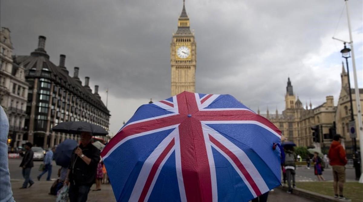 Un transeúnte se refugia de la lluvia en un paraguas con la bandera británica, cerca del Big Ben, este sábado.