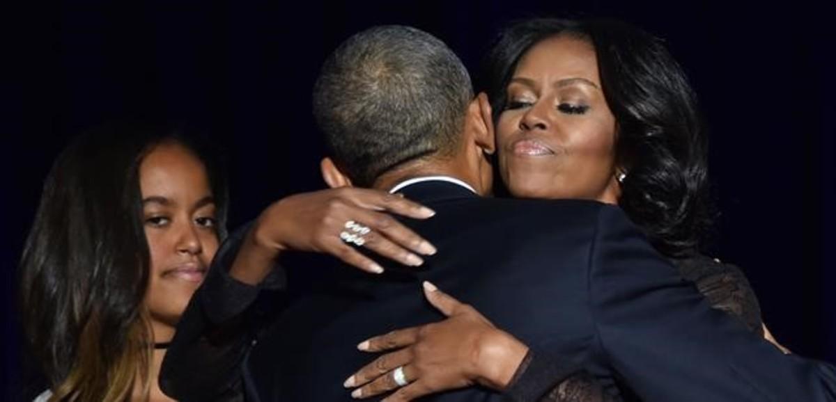 Obama abraza a su mujer, Michelle, en presencia de su hija Malia después de su discurso de despedida en Chicago.