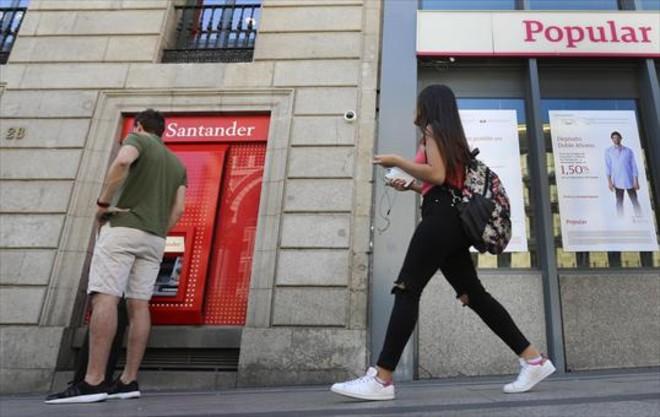 Una oficina del Santander, junto a otra del Popular, en Madrid.