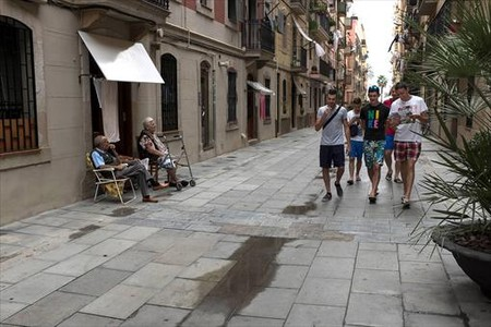 Dos vecinos tomando la fresca en la calle, s�mbolo del barrio, observan pasar a un grupo de turistas.