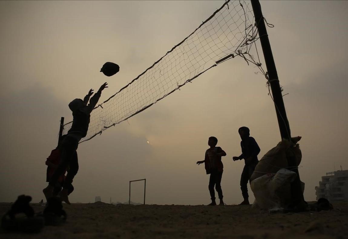 Nens palestins juguen a voleibol amb una pilota de plàstic, a prop de casa, a la ciutat de Gaza.