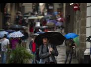 Viandantes se protegen de la lluvia con paraguas por las calles del barrio gotico.