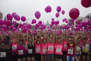 Participantes en la carrera sujetan globos en solidaridad con las enfermas de cáncer de mama, ayer.