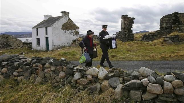 Dos oficiales se llevan la urna de la isla irlandesa de Inishbofin.