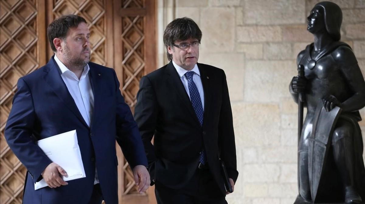Oriol Junqueras y Carles Puigdemont se dirigen a la reunión del Consell Executiu, este martes.