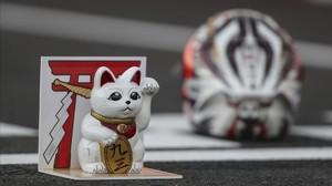 El gato que atrae a la suerte, junto al casco de Marc Márquez, en el box de Motegi en 2016.