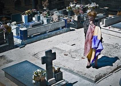 La hija de José Celda, sobre la fosa común que alberga los restos de su padre, en Paterna (Valencia).