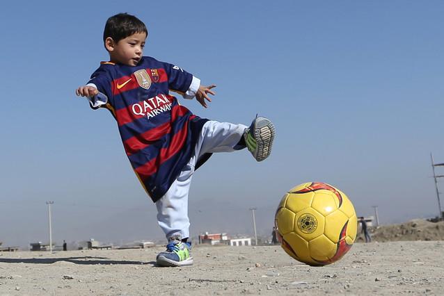 El pequeño Murtaza Ahmadi, ataviado con la camiseta del Barça firmada por Messi, su ídolo, juega con un balón en Kabul, este viernes.