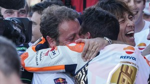 Emilio Alzamora, visiblemente emocionado, abraza y felicita a su pupilo, Marc Márquez, tras la conquista de su sexto título mundial de motociclismo en Valencia.