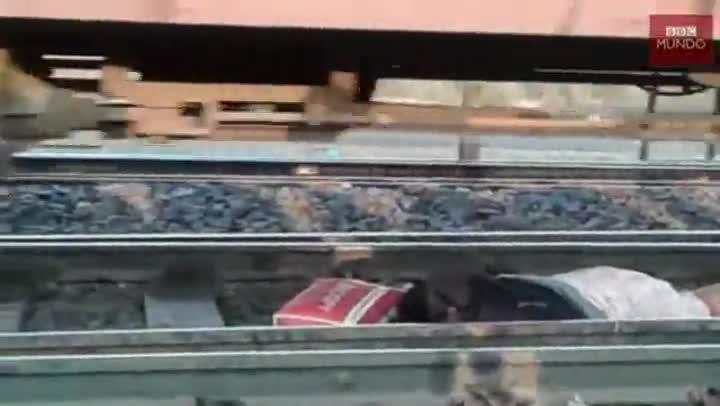 La mujer se queda inm�vil estirada en las v�as mientras el tren le pasa por encima.