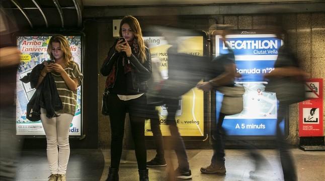 Unas jóvenes miran su móvil en un andén del metro.