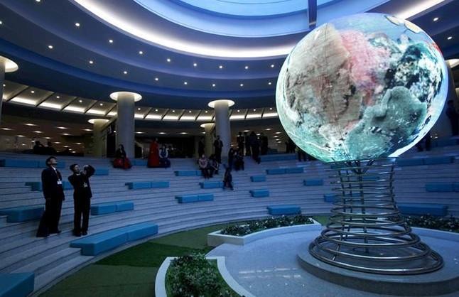 Un visitante toma fotos de un modelo de globo terrestre en el complejo Sci Tech de Pionyang, este miércoles.