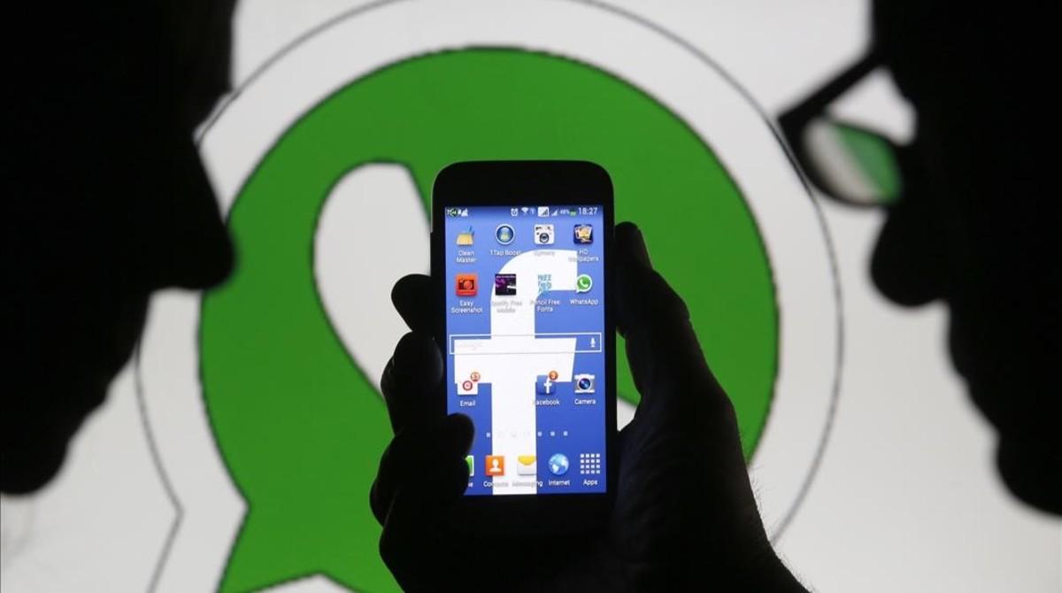 Dos usuarios ante los logos de Facebook en el móvil y Whatsapp.