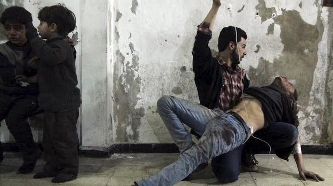 Un hombre da asistencia m�dica a un heridotras un ataque de las fuerzas del r�gimen al barrio de Duma, en Damasco.