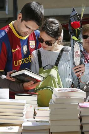 Una pareja, ella con una rosa y él con una camiseta del Barça, en una parada de libros en las Ramblas de Barcelona durante la Diada de Sant Jordi.