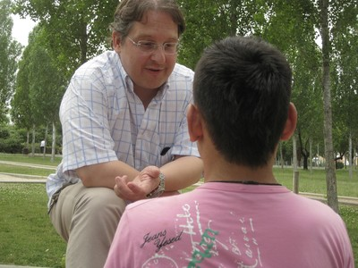 El salesiano Joan d'Arquer conversa con Helder P. (sentado), en un parque cercano al piso donde el religioso acoge al joven.