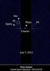 Imagen tomada por el 'Hubble' que muestra las cinco lunas alrededor de Plutón. El círculo verde marca el satélite recién descubierto, llamado P5, en una imagen del pasado día 7.