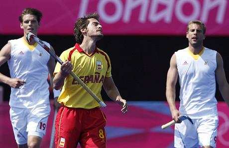 L'espanyol Álex Fábregas es lamenta davant els belgues Félix Denayer i Máxime Luycx, durant el partit pel cinquè puesto en hoquei sobre herba