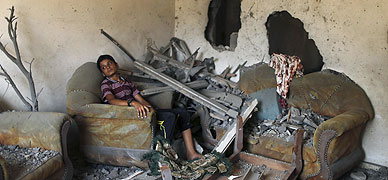 Un ni�o palestino se sienta en el sal�n de su casa destruida, ayer en Gaza.