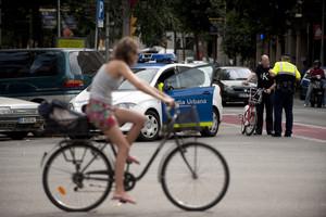 Una ciclista observa cómo un guardia urbano multa a una persona que va en bicicleta por saltarse un semáforo.