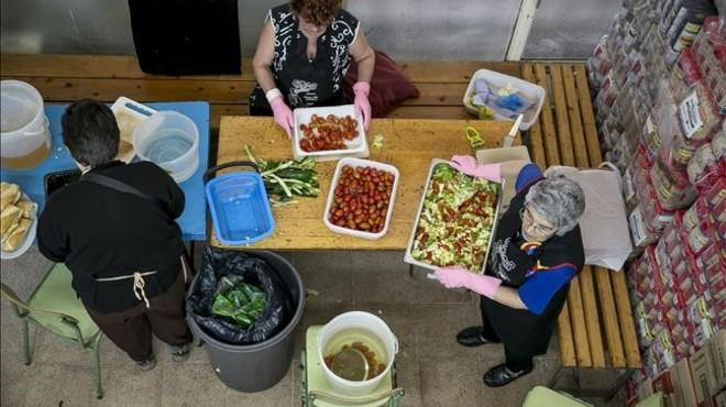 Vecinas del barrio del Bes�s preparan la comidapara el comedor solidario Gregal.