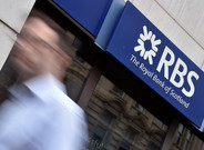 A man walks past a branch of The Royal Bank of Scotland in central London