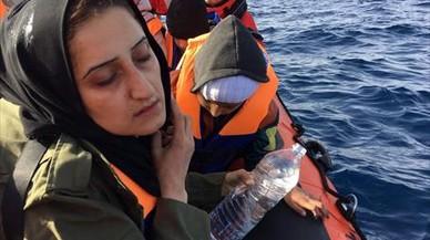 Una madre llora rodeada de sus hijos en una barca de rescate de Open Arms.