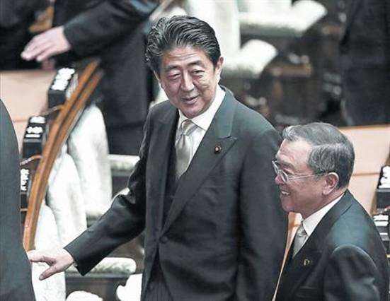 El primer ministro japonés, Shinzo Abe (centro), conversa con el ministro de Economía, Yoichi Miyazawa.