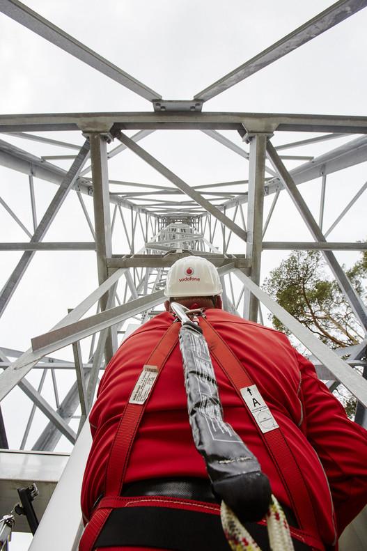 Operario revisa torre de antenas de Vodafone