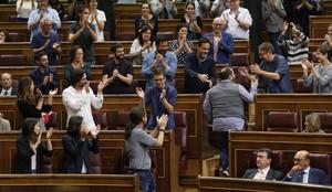 Joan Mena, de espaldas, sube a su escaño entre los aplausos de Podemos.
