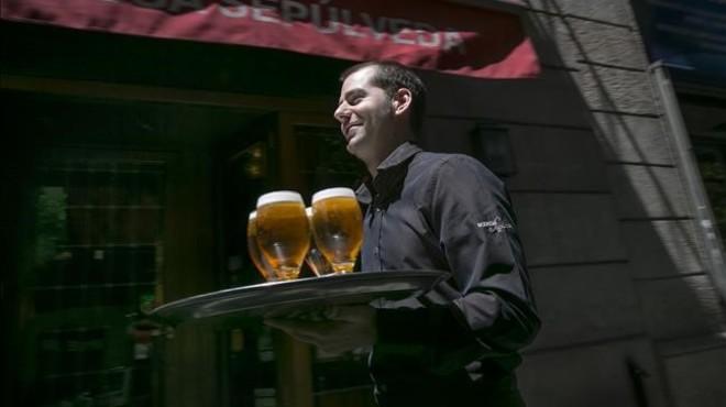 Gonz�lez, con una bandeja llena de cervezas en la Bodega Sep�lveda, donde trabaja.