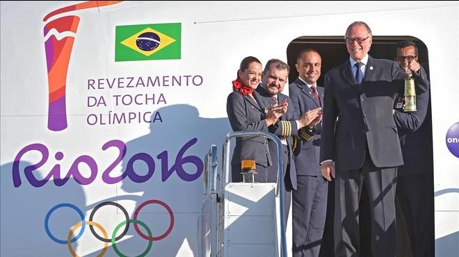 El presidente del Comite Ol�mpico Brasile�o, Carlos Arthur Nuzman, transporta la linterna con el fuego ol�mpico a su llegada a Brasilia.