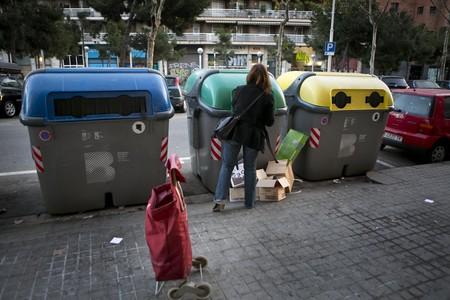 Una mujer deposita residuos en contenedores, en la calle Pujades, en Barcelona.