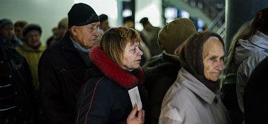 Varias personas aguardan en un centro de distribuci�n de ayuda humanitaria en Donetsk, ayer.