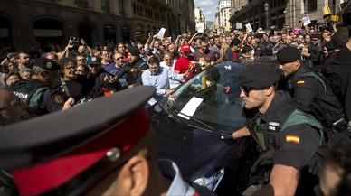 Diversos manifestantes tratan de impedir la salida del vehículo en la que la Guardia Civil se lleva uno de los detenidos en la Conselleria d'Afers Exteriors.