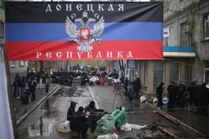 Ucranianos separatistas, junto a una comisaría de policía y bajo una pancarta que reza: República de Donetsk.